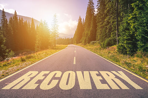 Recovery word written on road in the mountains.jpg