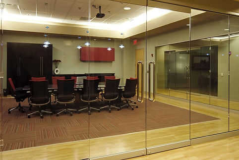 Corporate office with glass surrounded confernce room was  reclaimed from the distressed mall building. DE|SL LLC