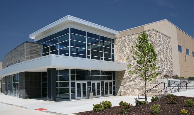 St. Dominic High School new gymnasium and performing arts center main entrance with stone, glass and masonry. DE|SL LLC