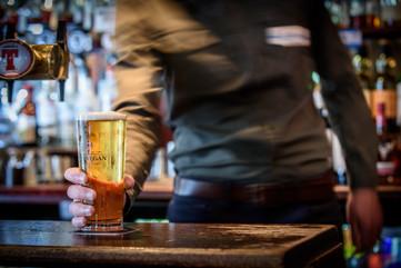 Barman holding beer glass