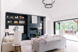 Living room design featuring dark builtins, black chandelier, black sliding doors and furn