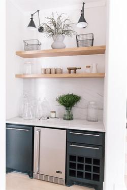 White oak floating shelves, bronze sconces, quartzite counter tops, wine area by Laura Des