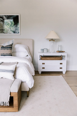 Bedroom design with white nightstand, glass lamp, linen bed and artwork by Laura Design an