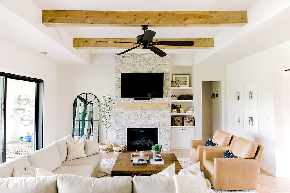 Living room design using Carmel leather accent chairs, natural textures, and neutral decor by Laura Design and Co, Dallas interior designer