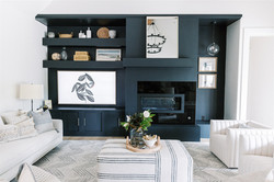 Living room design with black chandelier, gray sofa, dark builtins and accessories by Laur