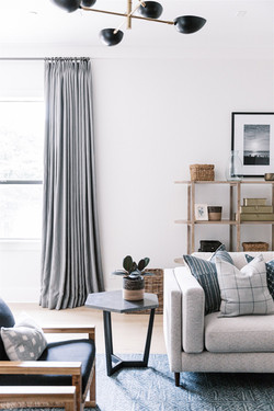 Gray linen curtains, black chandelier, gray sofa, and blue wool rug, living room design by