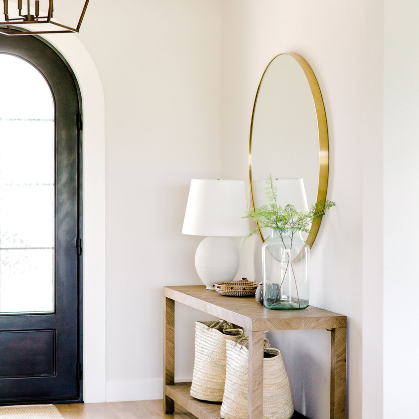 Entry way design with herringbone console, brass round mirror, and neutral decor by Laura Design and Co, Dallas interior designer