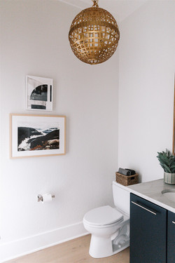 Bathroom design featuring floating vanity, wood framed mirror, brass light fixture and acc