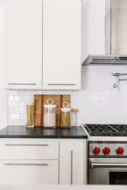 Black soapstone countertops, white subway tile, white cabinets design by Laura Design and