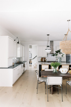 Open concept Kitchen and dining room design with glass pendants, quartzite countertops, wa