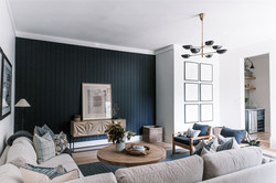 Living room design with black light fixture, black and white prints, gray sofa, round coff