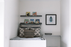 Kids builtin bunk with artwork, floating shelves and oversized pillows by Laura Design and