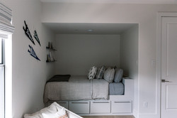 Kids bedroom design featuring striped rug, striped roman shade, striped pouf, linen beddin