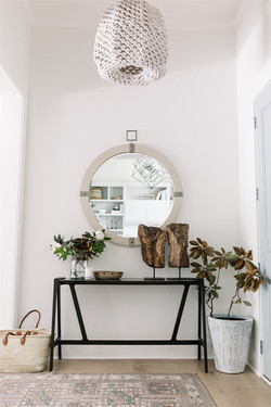 Entry area design featuring woven pendant, blue front door, black console table, round mir