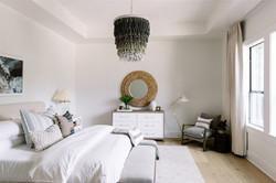 Bedroom design featuring linen drapes, white dresser, white nightstands, chandelier, round
