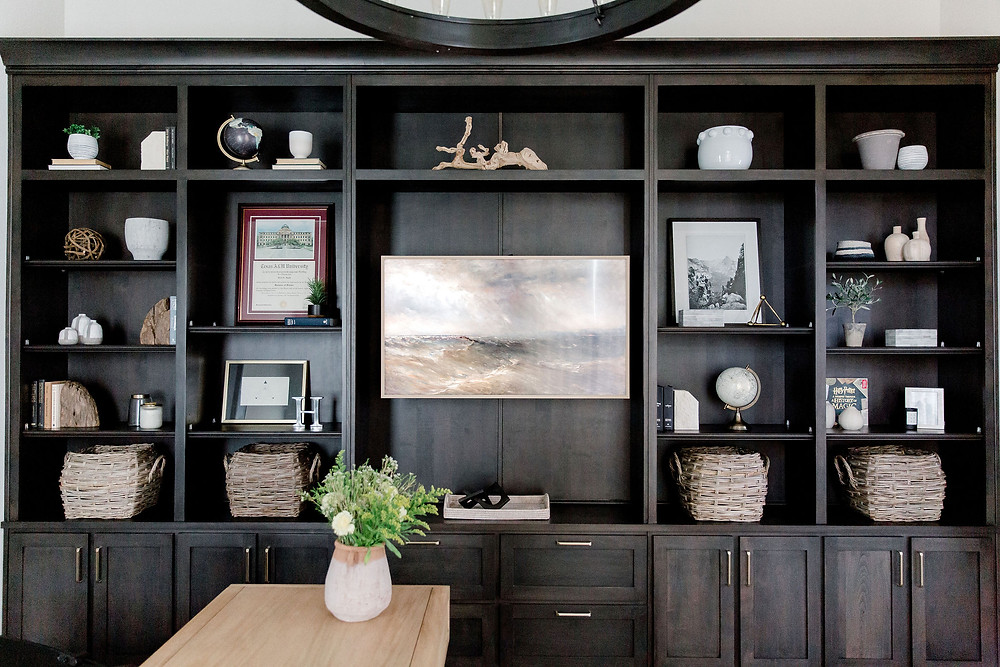 Home office design with wool rug, light-stained desk, artwork and dark built-ins by Laura Design and Co, Dallas interior designer