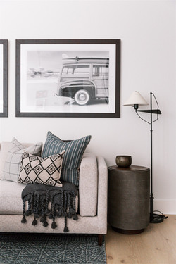 Living room design with black and white prints, gray sofa, blue accent pillows, gray throw