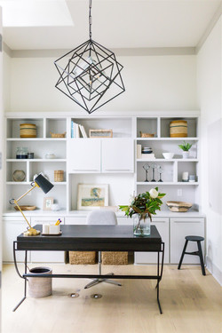 Office design featuring black desk, gray builtins, black chandelier, and striped roman sha