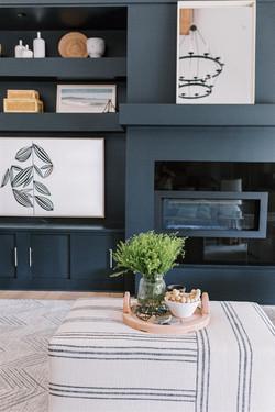 Striped ottoman, chevron rug, dark builtins, and accessories by Laura Design and Co, Dalla