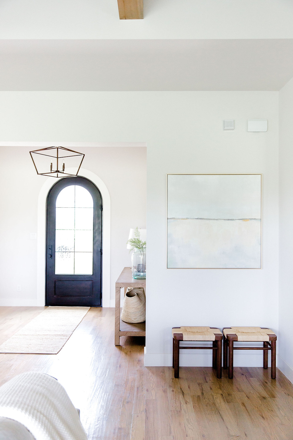 Entry space by Laura Design and Co using wood stools & neutral artwork