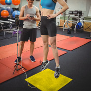 Fit woman measuring her jump with traine