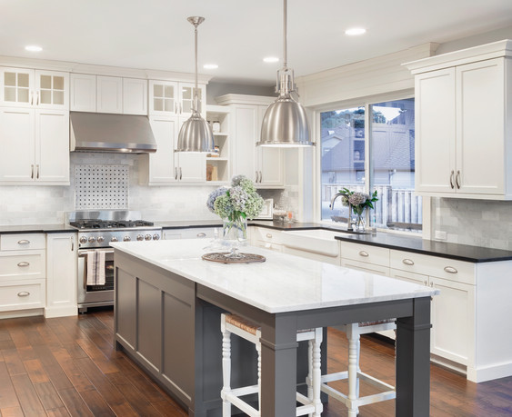 beautiful kitchen in luxury home with island, pendant lights, cabinets, and hardwood floors. tile back splash, stainless steel oven,range, a