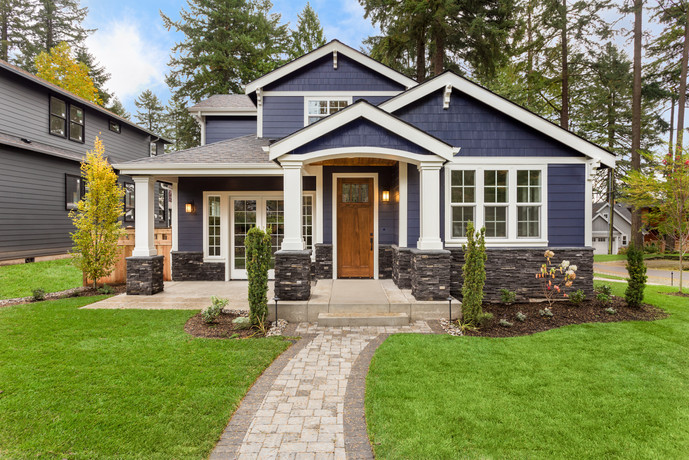 Beautiful exterior of newly built luxury home. Yard with green grass and walkway lead to ornately designed covered porch and front entrance..jpg