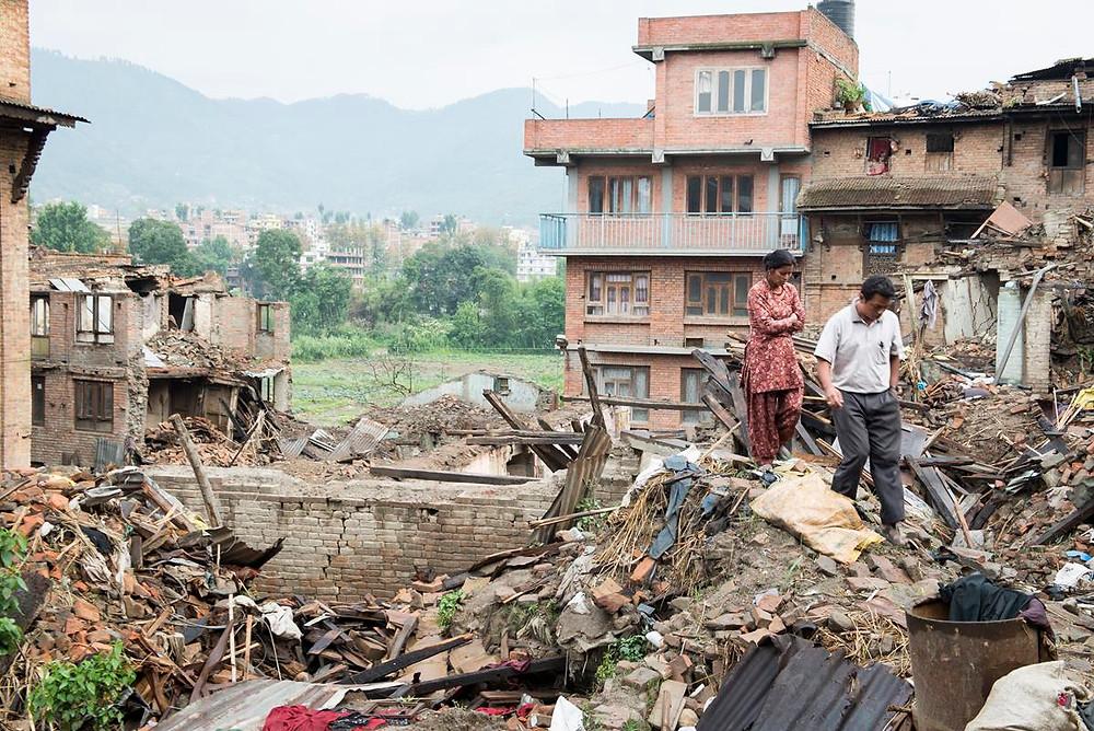 Vecinos observan entre los escombros los daños provocados por el sismo