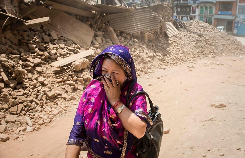 Una mujer se cubre del polvo provocado por los escombros