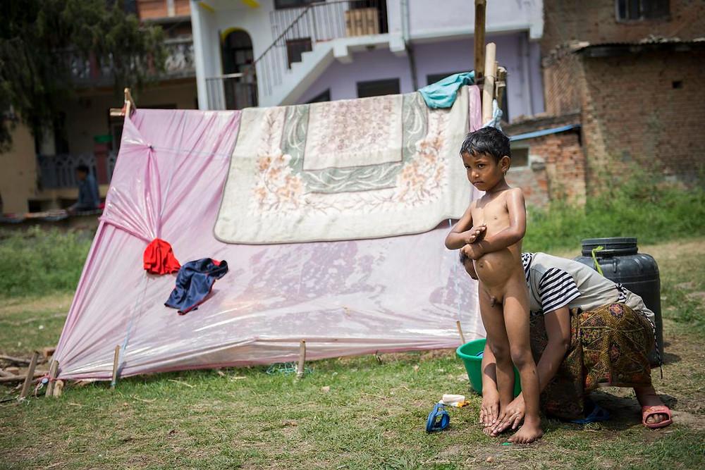 Una madre baña a su hijo en uno de los tantos campamentos improvisados