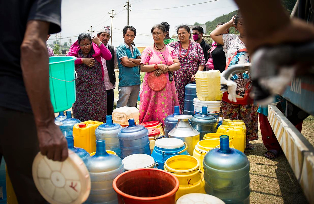 Refugiados del campamento esperan por el agua del camion cisterna