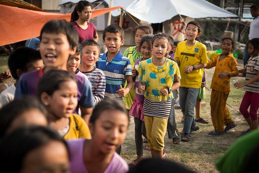 Niños jugando en uno de los campamentos para refugiados, acompañados de una asistente social
