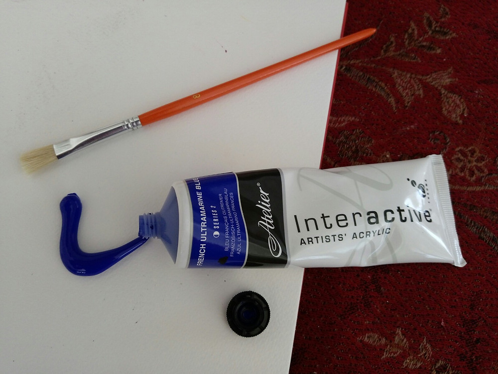 A photograph of a paint brush, sketch pad, and blue paint coming out of the tube.