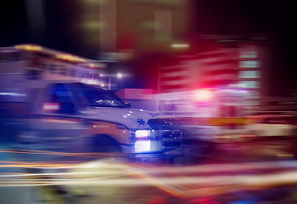 An ambulance speeding through traffic at
