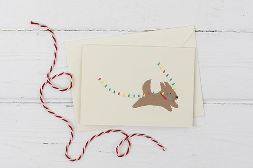 Naughty brown dog with fairy lights- Christmas greetings card