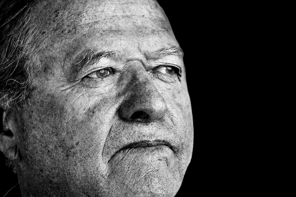 Dramatic and powerful black and white portrait of a senior man with pale eyes looking away great facial details