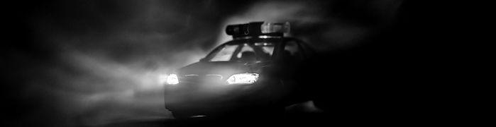Police car chasing a car at night