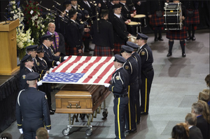 Police officers folding a US flag over the coffin of a fallen comrade