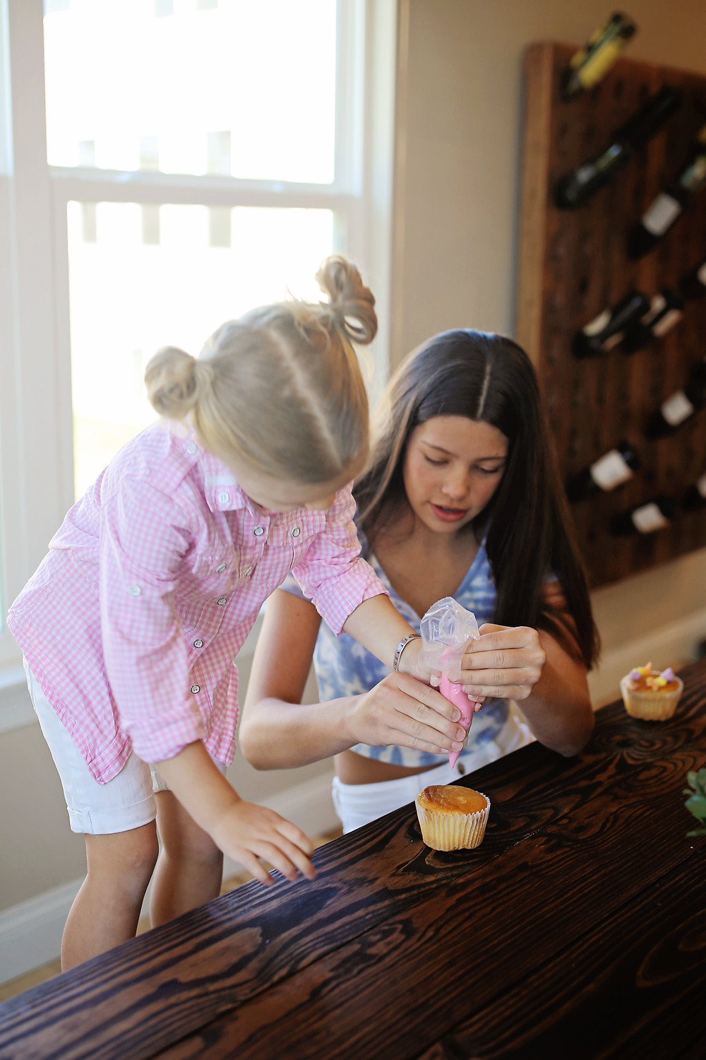 Big sister is helping little sister add icing to a cupcake