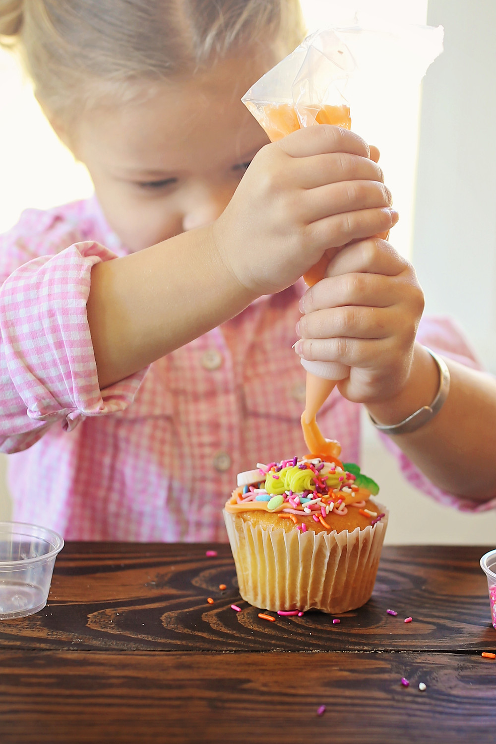 Adding icing on top of sprinkles on a vanilla cupcake