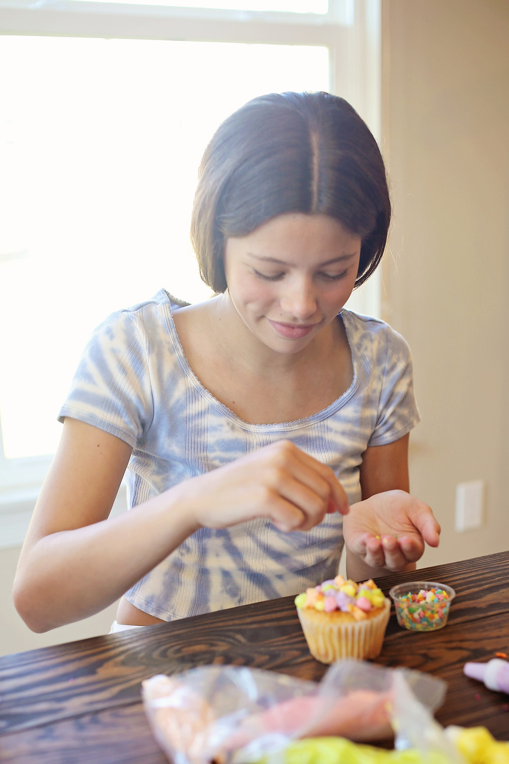 Putting sprinkles on a cupcake