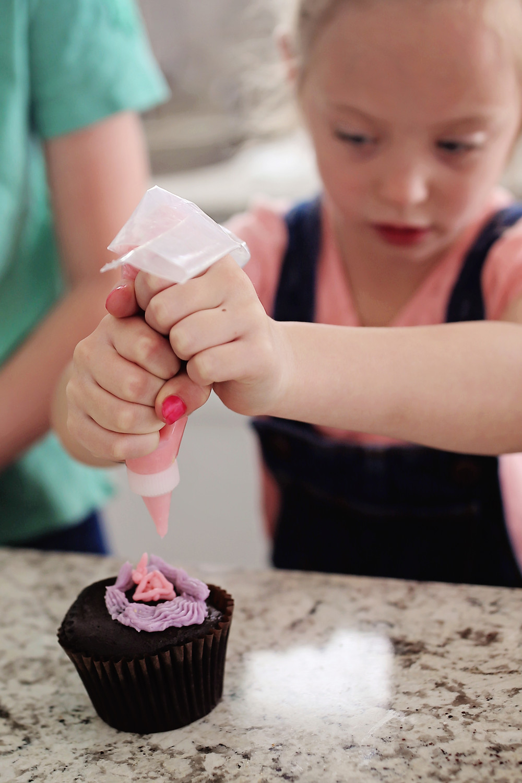 Adding icing to a chocolate cupcake