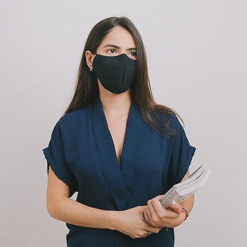 Mujer usando mascarilla antifluidos lavable en una empresa.
