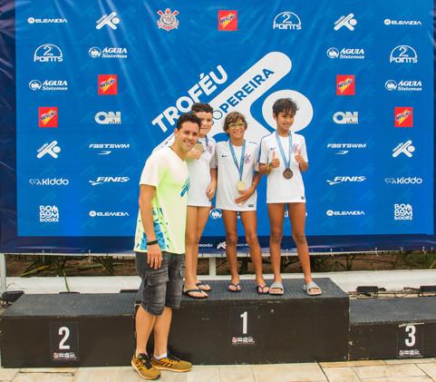 Nadadores recebem medalhas e posam junto ao Backdrop oficial com as marcas patrocinadoras