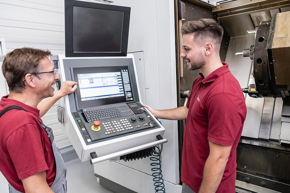 Mitarbeiter reden an einer Maschine der Diamant- Gesellschaft Tesch GmbH