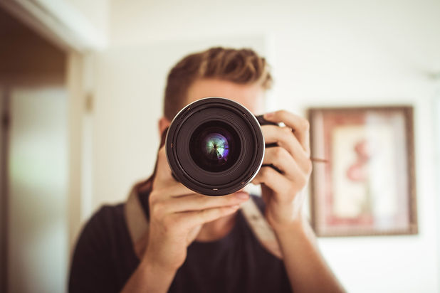 Fotograf mit einer Kamera in der Hand.