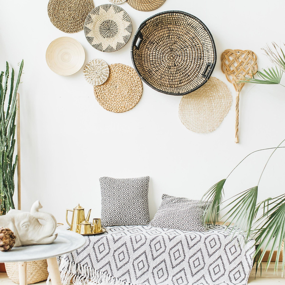 a cozy boho-inspired room with a bench, plants, and decorative baskets hanging on the wall