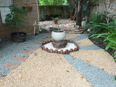 A muddy area turned into an Asian inspired stone area; in the center is a Japanese maple on a lava rock
