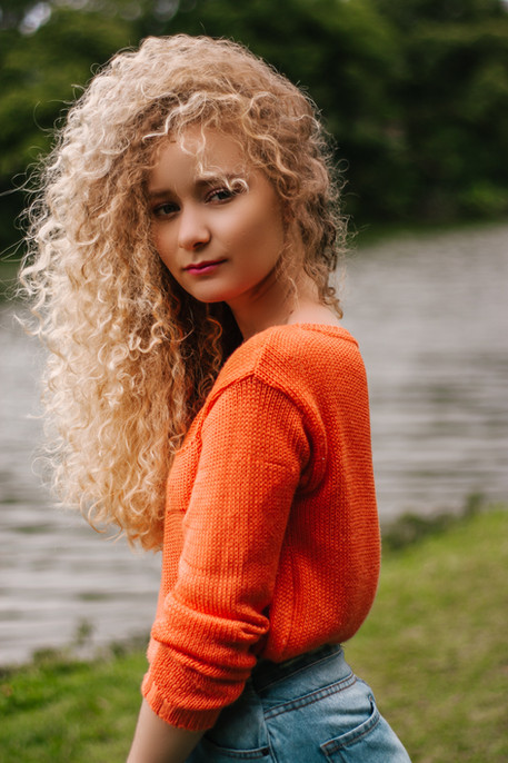 curly-haired-blond-woman-in-orange-shirt