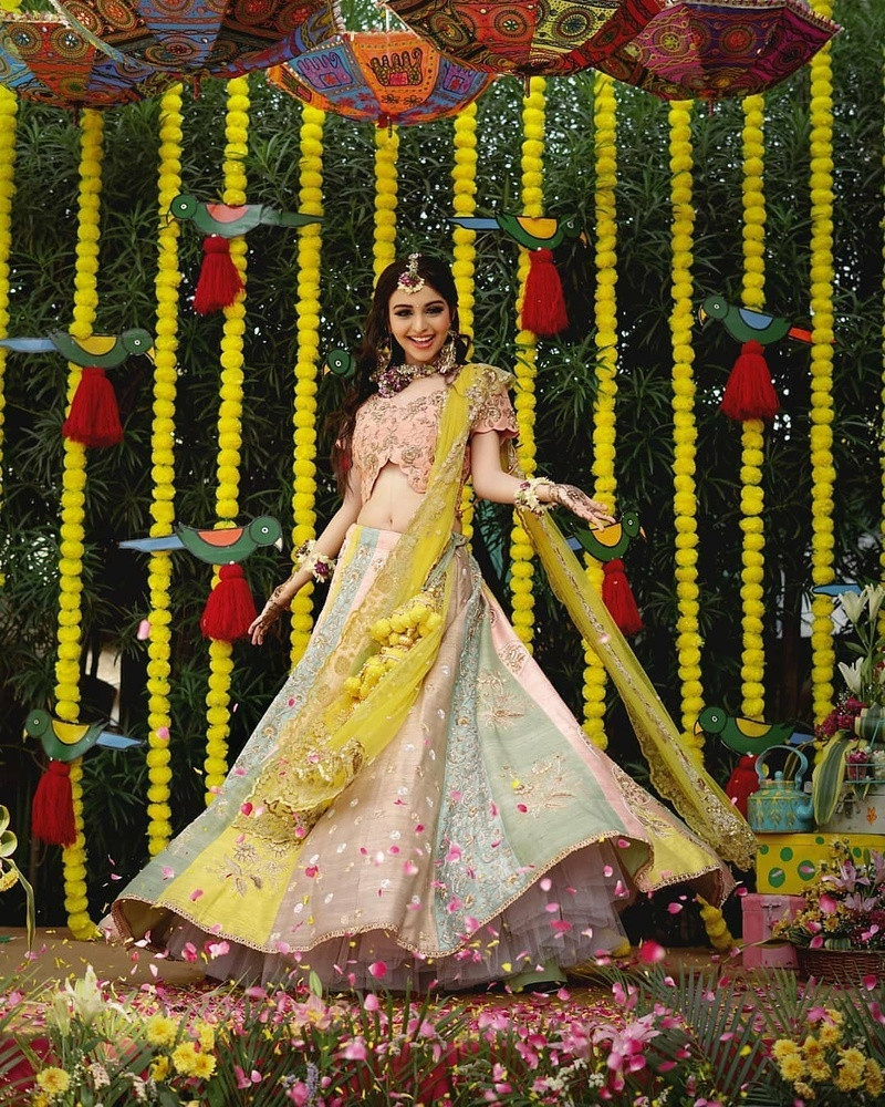 9. A multicolored lehenga skirt with pink base paired with dusty pink choli with golden work on it